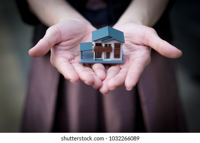 Model house in woman's hand., Little house toy. Selective focus. Copy space. Background.