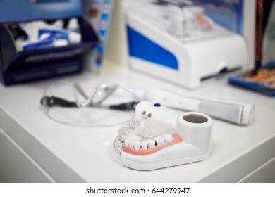 Model of human jaw with teeth, electrical toothbrush and glasses on table, shallow dof.