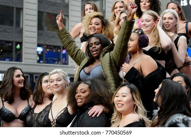 Model Jae Christine raises her arms in celebration during a group shot in Times Square, December 2, 2017.