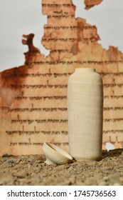 A model of a Jar used for the Dead Sea scrolls against a blurred background of the Isaiah scroll