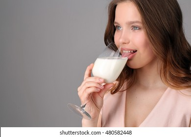 Model licking milk from a wine glass. Close up. Gray background