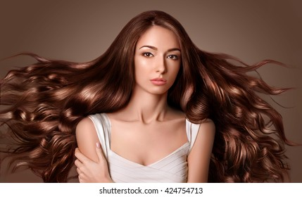 Model with long  brown hair. Waves Curls Hairstyle. Hair Salon.