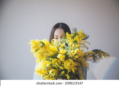 model with long chestnut hair with mimosa in her hands
