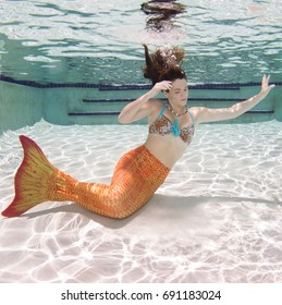 A model with long hair in a pool underwater.