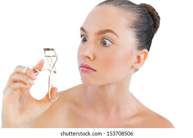 Model looking at her eyelashes curler on white background