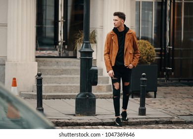 Model looking man stand on the city street with cars background, look on his watch and around
