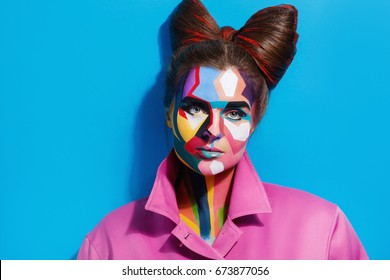 Model looks like character from comics pages. Woman with a creative pop art makeup on her face.