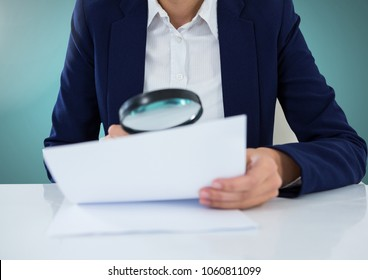 Model with magnifying glass looking at papers