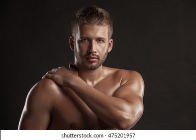 Model man with an open  chested on a dark background , muscular body of a young man in jeans . Shot in a studio .