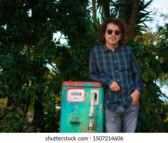 Model man posing next to an old gasoline pump
