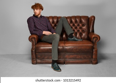 A model man sits on a brown leather couch in a relaxed pose. Thinking Confident, successful, rich. dressed in jeans and a shirt, redheaded, shoes, sucked on the back of the couch, looks at the sides.