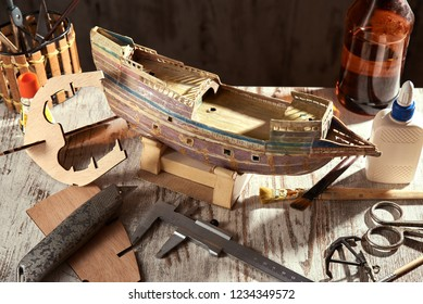 MODEL OF THE OLD SHIP FRIGATE MADE IN HANDS FROM THE CARDBOARD. NEAR GLUE, BRUSHES, SCISSORS AND STANGENCIRCLE