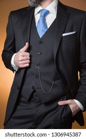 model on an orange background with classic dress complete with striped tie, handkerchief in the pocket and pocket watch