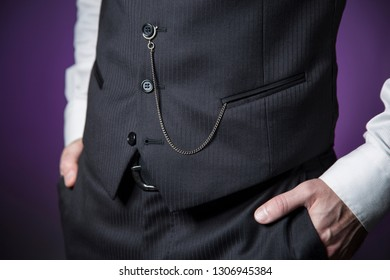 model on purple background with pinstriped waistcoat accompanied by a classic pocket watch attached to the button