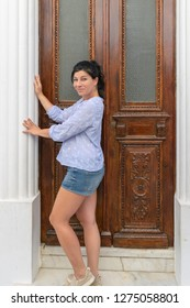 Model posing against the traditional houses at Andros island in Greece.