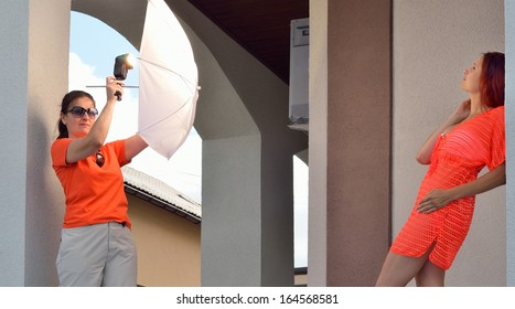 A model is posing against the wall outdoors. An assistant is holding a photoflash with an umbrella.