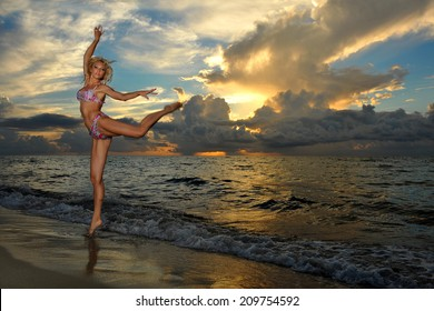 Model posing in bikini at early morning sunrise over the ocean at tropical location