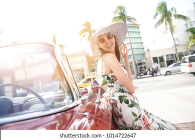 Model posing by old-fashioned car