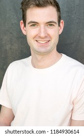 Model posing for the camera for a headshot in front of textured black background wearing a t-shirt, no facial hair. Clean cut guy, white, brown hair, in his 20s. Healthy lifestyle concept.