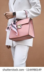 Model is posing with a coral bag with a pink silk scarf on the wall background outdoors. She wears a white pantsuit. Closeup vertical photo.