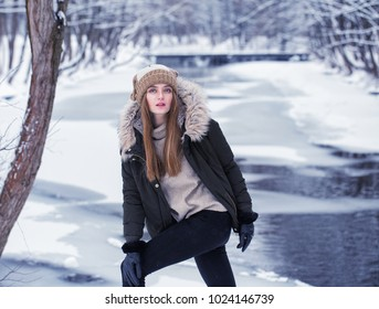 Model posing girl posing against a background of winter nature. Dressed for winter beautiful appearance, long hair