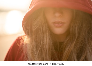 Model posing in a hooded garment covering her eyes
