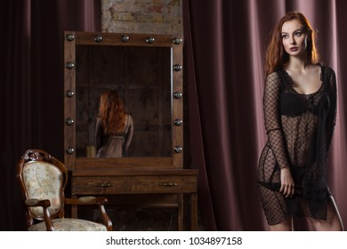 model posing near the mirror in the boudoir room. woman in erotic underwear stands modestly shy