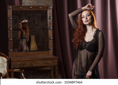 model posing near the mirror in the boudoir room. woman in erotic underwear stands in a sexual pose. scene of temptation