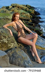Model posing pretty at rocky beach in designers animal printed swimsuit