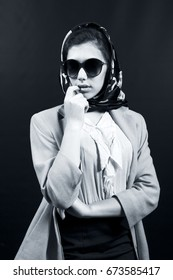 Model posing vintage style with sunglasses and headscarf