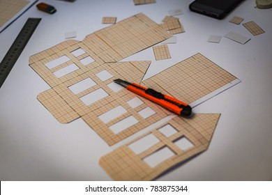 A model of prefabricated houses made of paper. Suitable for Christmas decoration and architectural desks. The machete is cut out of millimeter paper. Shallow depth of focus. Concept Home.