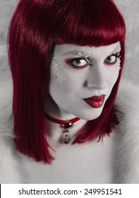 Model in red wig with dramatic red and white make-up wearing red choker.