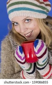 Model Released. Attractive Young Woman Wearing Woolen Hat Drinking Tea