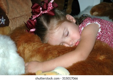Model released image of young caucasian preschool girl sleeping on a pile of stuffed animals on the floor