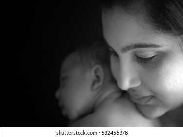 Model released photograph of a mother looking at her baby