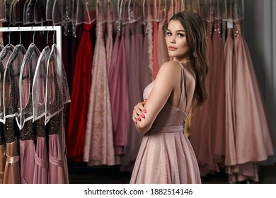 Model selecting an outfit for occasion in dress hire service with many options on background.
