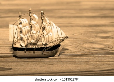 model ship with sails on a wooden table background. travel, cruise, sailing from the tool