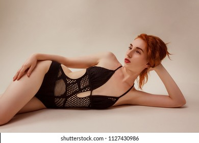 Model shoot in studio. Skinny girl with red long hair posing in the black knitted swimsuit bikini lying on the floor in warm tones