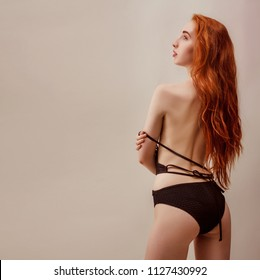 Model shoot in studio. Skinny girl with red long hair posing in the black knitted swimsuit bikini in warm tones