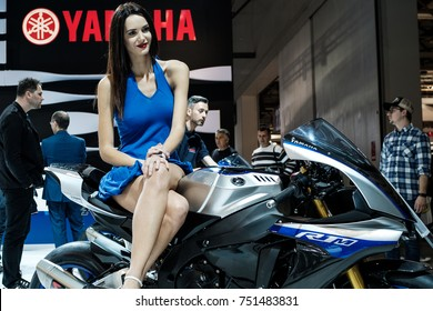 A model sitting on the saddle of a Yamaha R1M at the stand of the Japanese motorcycle manufacturer at the Fiera di Milano during EICMA 2017, international exhibition cycle and motorcycle.