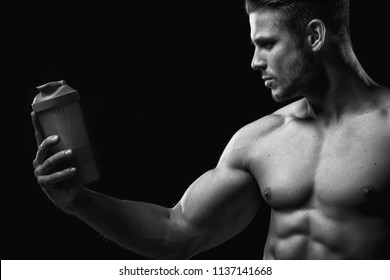 Model sports young man on dark background. Black and white portrait of muscle guy with protein drink in shaker. Bodybuilding nutrition supplements, sport, workout, healthy lifestyle concep.
