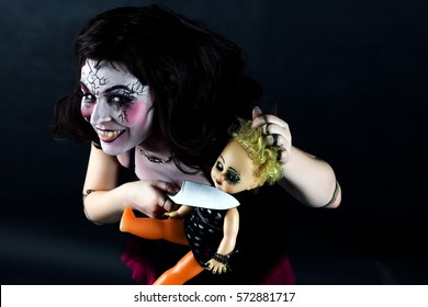 model in stage makeup doll head cut off with knife on dark background