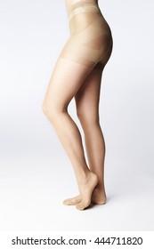Model standing on tip toe in tights, studio