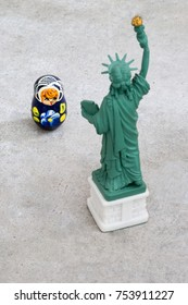 A model of the Statue of Liberty that is looking at a small Russian Matryoshka doll with the focus on the Matryoshka doll (concept)