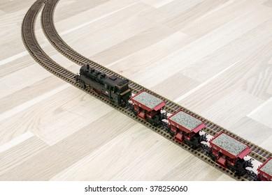 Model steam train on wooden floor, game for kids