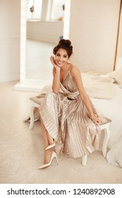 Model in the studio. Warm colors. Charming brunette woman in beige dress sits on the sofa before a mirror and smiles