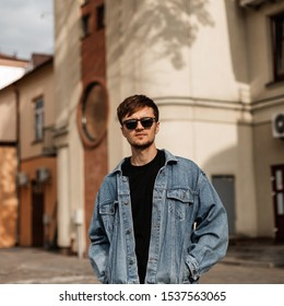 Model of a stylish young man in fashionable sunglasses in a blue vintage jacket near vintage buildings on a sunny summer day. Attractive guy travels around a town in the city. Trendy men's clothing.