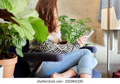 Model in sweater chilling in cozy armchair with wineglass and using tablet.