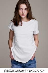 Model test portrait with young beautiful fashion model posing on grey background. Wearing white t-shirt and jeans.