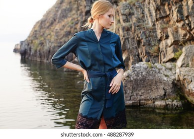 model tests of fashion blond girl in dress posing near the rock with grass